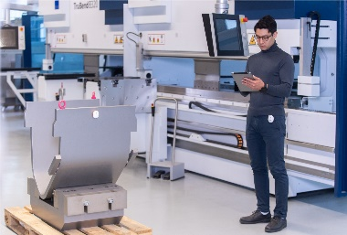 An employee uses omlox to find a workpiece on a pallet. Positioning technologies and products from different vendors can be combined via this uniform standard.